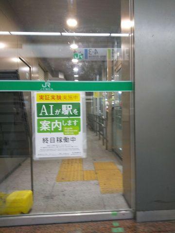 改札の張り紙。「検証実験中。AIが駅を案内します。終日稼働中」