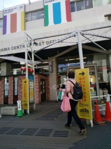 中央郵便局の玄関。黄色地に赤字で「アソビルは右手。みなみ東口へ。」という立て看板。