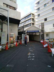 両側に赤いパイロンが立つ小道。その先にプレハブのトンネル。上に「横浜駅みなみ東口。JR」の看板。